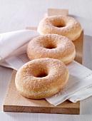 Sugared doughnuts on a chopping board