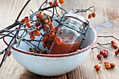 Hawthorn jelly and hawthorn twigs in an enamel bowl