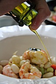 White beans with celery, pepper and prawns being drizzled with olive oil