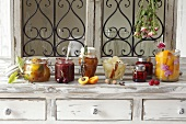 Various types of preserved fruit: apricot jam with lavender, pears in vinegar, raspberries in sugar syrup, peaches with dried roses