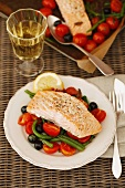 Salmon fillet on a tomato and bean salad with olives