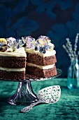 Chocolate sponge cake decorated with white chocolate and lavender cream and sugared edible flowers