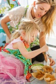 Woman and Young Girl Frosting Cupcakes