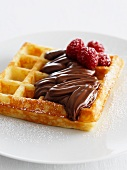 A waffle topped with chocolate spread and raspberries