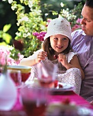 Little girl sitting on her father's lap eating cherries