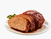 Partially Sliced Meatloaf on a Plate; White Background