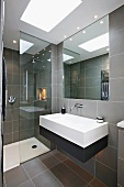 Designer bathroom with gray tiles and embedded lighting in a suspended ceiling