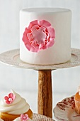 Cake with a Pink Frosting Flower on a Cake Stand