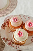 Three Vanilla Cupcakes with Pink Flower Decorations
