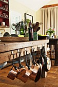 Massive wooden table with copper pans hanging from one side and set with shallow basket, wine bottles and storage containers in dining area on rustic wooden floor
