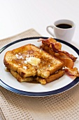 Two Slices of French Toast with Butter and Maple Syrup; Two Pieces of Bacon and a Cup of Coffee