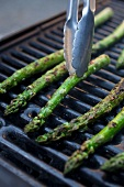 Tongs Turning Asparagus Spears on the Grill