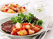 Beef with a side of tomatoes and potatoes and a mixed leaf salad