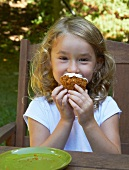 Little Girl Eating a Cupcake at an Outdoor Table