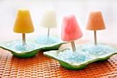 Vier Fruchteis-Popsicles in hellblauem Eis