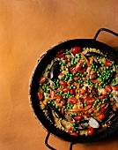 Paella in a Skillet; From Above; On Orange Background