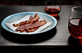Strips of Bacon on a Plate with Glasses of Blush Wine