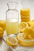 An arrangement of lemon juice, a lemon press and juiced lemons