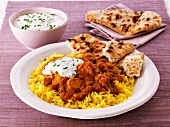 Chicken curry with rice, unleavened bread and a yoghurt dip