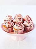 Cupcakes with strawberry cream and sugar sprinkles on a cake stand