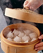 Dough parcels being steamed in a bamboo basket