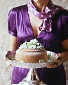 A woman in a purple dress holding a cake on a silver stand