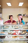 Two women standing at counter of bakery