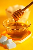 Honey on a honey spoon and sugar cubes