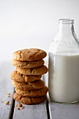 A stack of peanut biscuits next to a bottle of milk