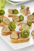 Canapes topped with kiwi and coppa roulade filled with tapenade