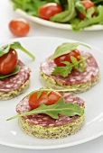 A plate of canapes with tapenade, salami, cherry tomatoes and rocket