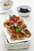 Crostini topped with tomatoes and olives
