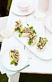 Bread rolls filled with lamb, avocado and mint, on a table outdoors