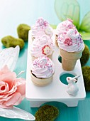 Chocolate cupcakes in ice cream cones with pink buttercream topping