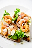 A slice of toast topped with salmon, prawns and Parmesan