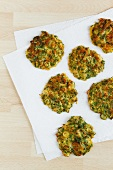 Freshly made courgette cakes on a piece of kitchen paper