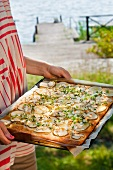 Pizza with pears and feta cheese on a baking tray (Sweden)