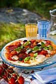 A tomato, mozzarella, sausage, olive and basil pizza