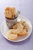 Piped biscuits with sprigs of thyme, on a white plate and in a cup