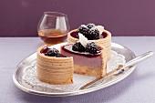Zwei Baumkuchentörtchen mit Brombeercreme gefüllt, dazu ein Glas mit Whisky