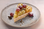 A slice of grape tart on a grey plate