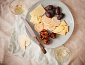 Cheddar Cheese with Crackers, Figs and Prunes on a Plate; With White Wine; From Above
