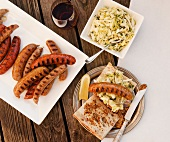 Grilled Sausage Sandwich with Cole Slaw, Pickles, Mustard and a Platter of Grilled Sausage; From Above