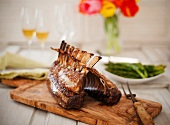 Rack of Lamb on a Cutting Board with Asparagus and Wine in the Background