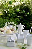 White porcelain crockery and sweet petits fours on a table outdoors