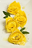Four tortellinis with sage leaves
