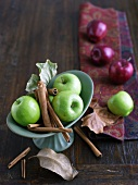 Granny Smith Apples with Cinnamon Sticks; Red Apples in Background