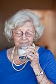 Ältere Frau trinkt ein Glas Milch