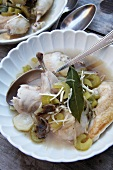 Cook spring chicken with stock, vegetables and truffles
