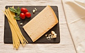 A Wedge of Parmesan Cheese with Dried Pasta, Tomatoes and Basil on Slate